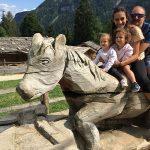 Famiglia a cavallo di una scultura in legno