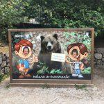 papa e figlia in posa vicino a cartellone di orso