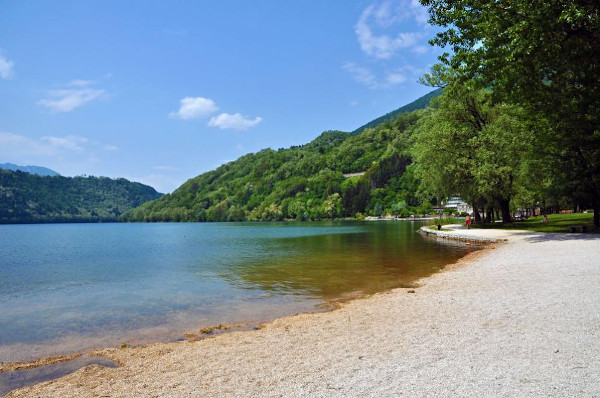 lago con spiaggia di sassolini e fitta vegetazione