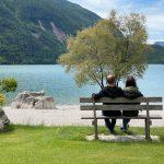 coppia seduta sulla panchina fronte lago
