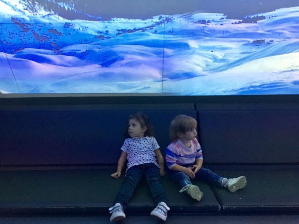 bambine sedute ad ammirare schermo con montagne