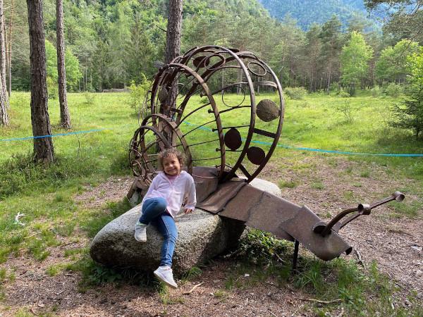 bambina seduta su sasso con scultura a forma di lumaca