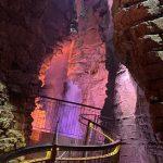 passerella in ferro dentro grotta con cascata