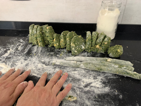 mani che impastano gnocchi verdi