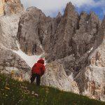 bambino con giacca rossa tcammina sulle alpi
