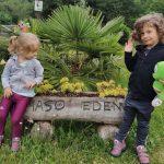 bambine sedute su fioriera in legno