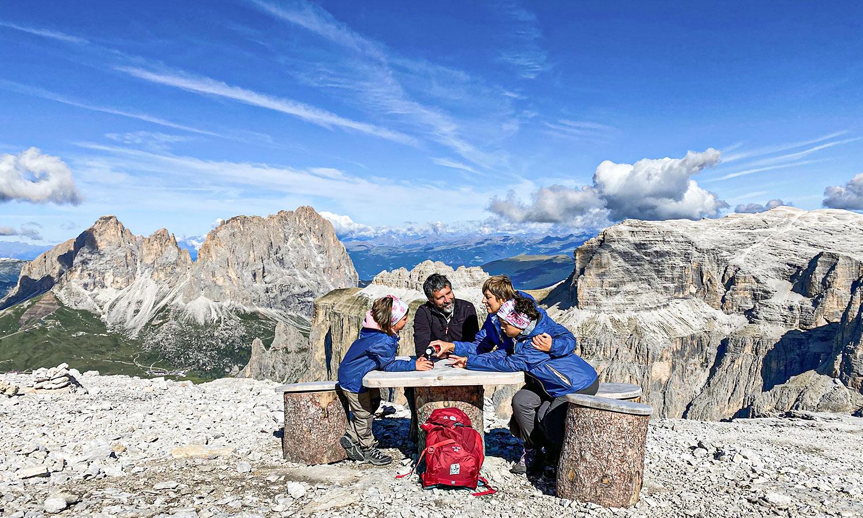 famiglia seduta a un tavolino sulla terrazza delle dolomiti