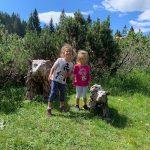 bambine in mezzo a sculture di legno a forma di orso
