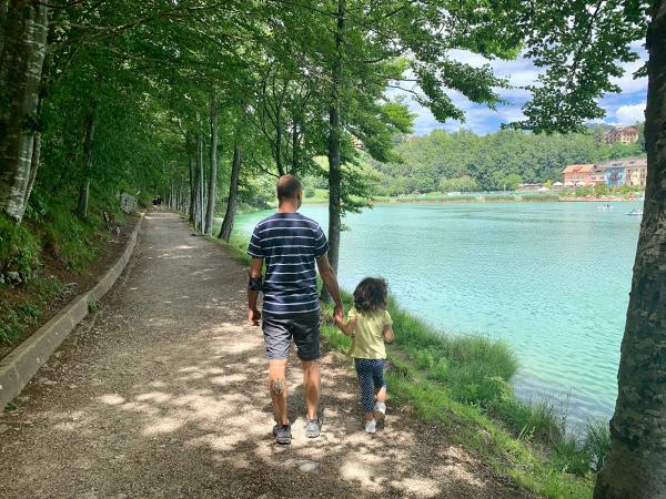 papà tiene per mano bambina mentre cammina sulle rive del lago