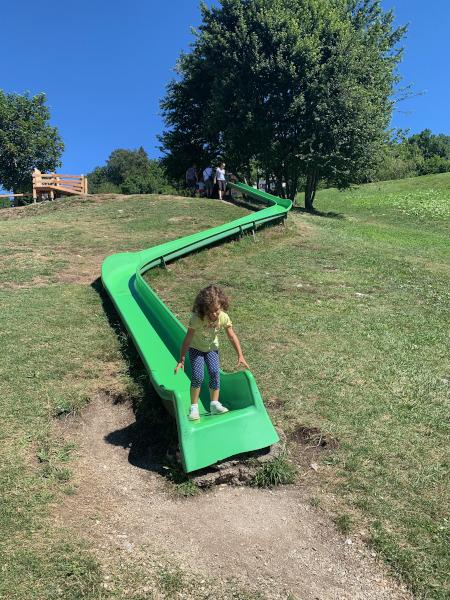 bambina su lungo scivolo verde