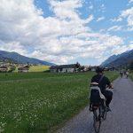 papà e bimba in bici che percorrono la ciclabile con le montagne sullo sfondo