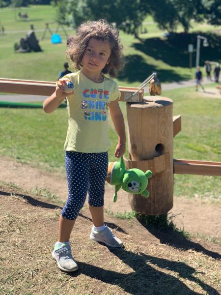 bambina con in mano una pallina di legno