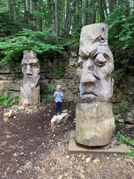 bambina in mezzo a due grandi sculture