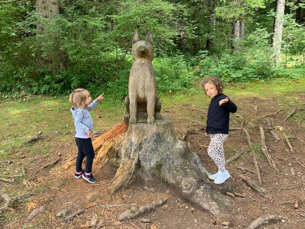 scultura lignea a forma di lupo con bambine