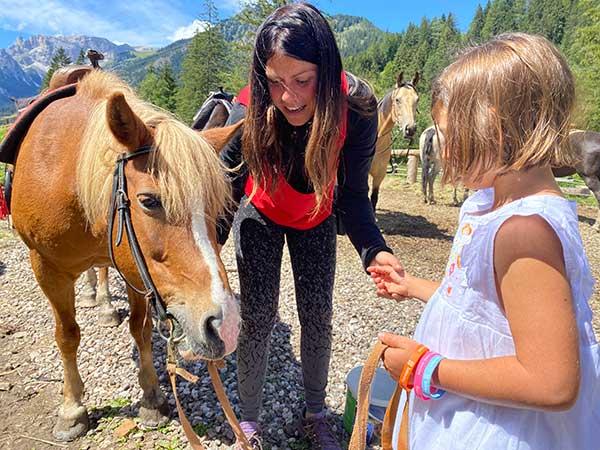 bimba dà da mangiare al cavallo