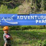 bambina davanti all'insegna del Dolomiti Action Adventure Park a Campitello