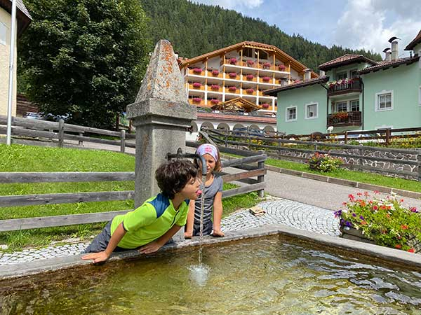 Cesa Tyrol sull osfondo e bimbi che bebono acqua a una fontana