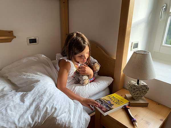 bambina legge libro sulle leggente delle dolomiti