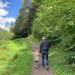 papà e bambina camminano su sentiero di montagna