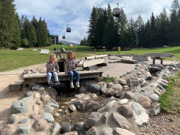 bambine sedute su ponte sopra ruscello