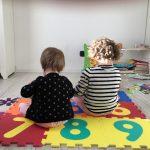 bambine sedute a terra su tappeto morbido