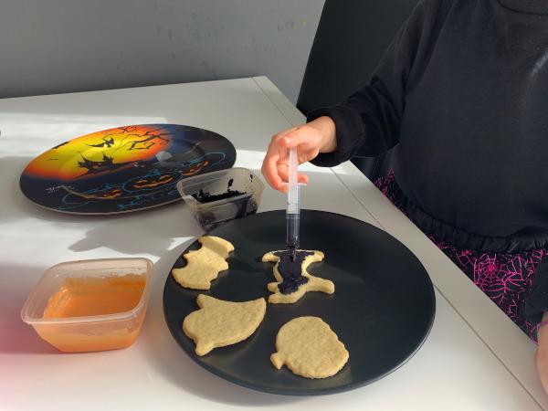 bambina decora biscotti con glassa colorata
