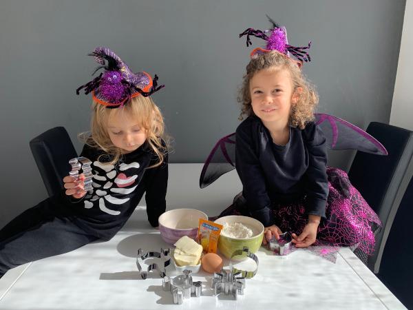 bambine sedute sul tavolo con ingredienti per biscotti
