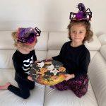 bambine tengono in mano piatto con biscotti a forma Halloween