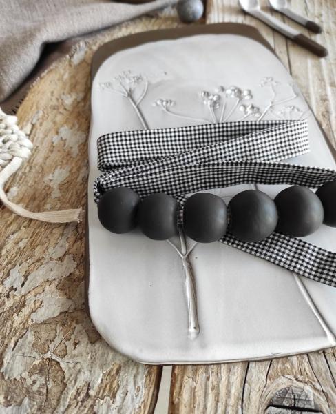 collana nera in cermica appoggiata su piatto bianco