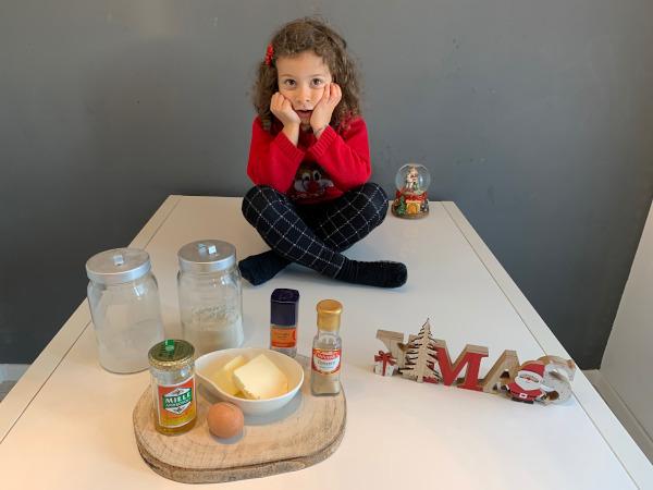 bambina seduta sul tavolo con ingredienti per fare i biscotti