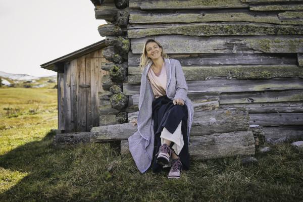 donna seduta su panca in legno vicino a baita