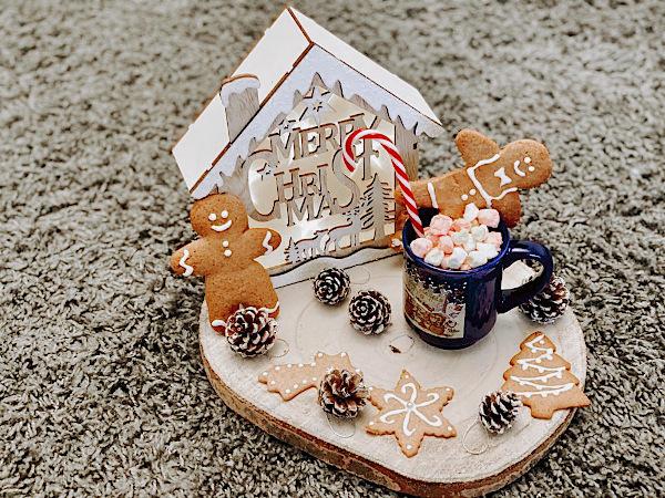 ceppo di legno con casetta natalizia e biscotti pan di zenzero