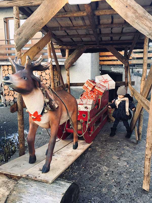 bambina vicino a slitta con renna e regali