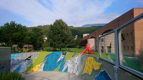 parco giochi con muro decorato con arte urbana