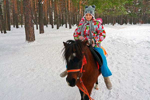 bambina a cavallo nella neve
