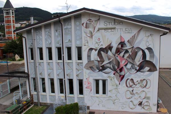 facciata di edificio con murales e scritte grigie