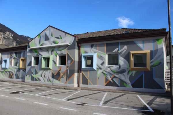 edificio completamento ricoperto da murales geometrico grigio