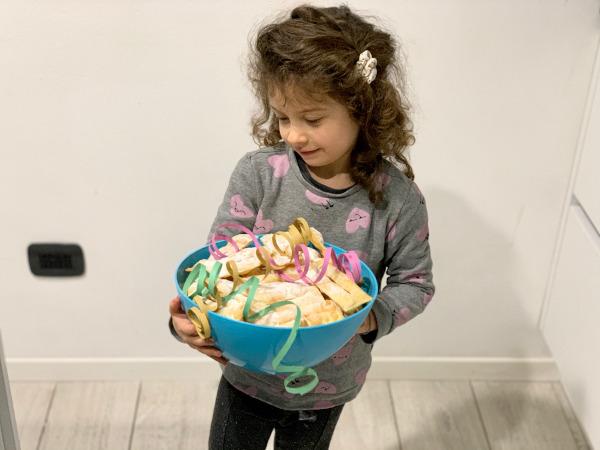 bambina con ciotola piena di dolci tipici trentini