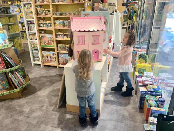 bambine che giocano con casa delle bambole in legno