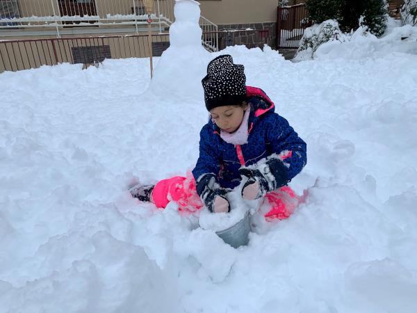 bambina gioca con secchiello e paletta con la neve