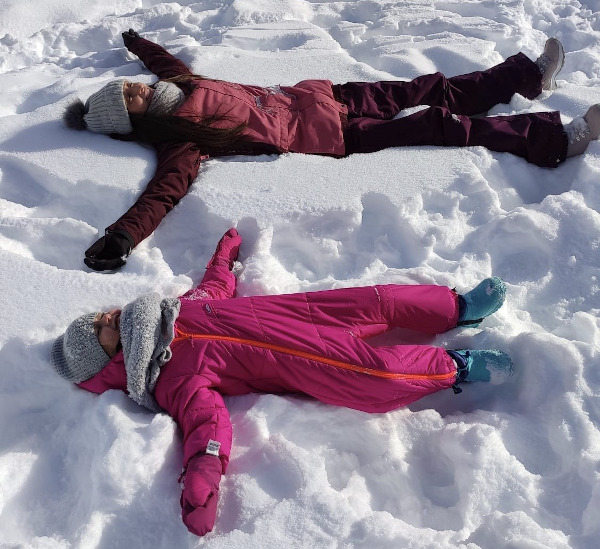 mamma e figlia sdraiate sulla neve