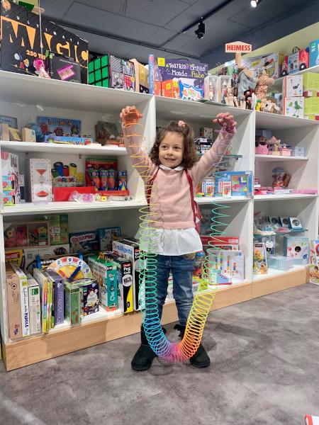 bambina che gioca con una molla multicolore