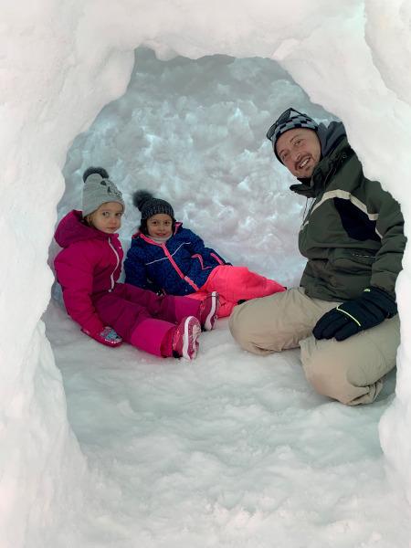 papà con bambine all'interno di un igloo