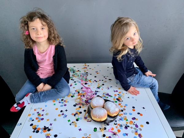 bambine sedute su tavolo pieno di coriandoli con piatto di krapfen