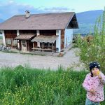 bambina con fiore e sullo sfondo baita