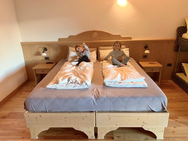 bambine sedute su letto matrimoniale in legno