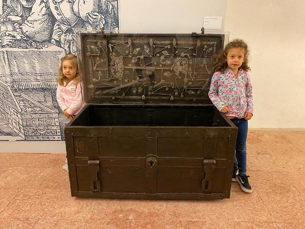 bambine ai lati di un grande baule antico