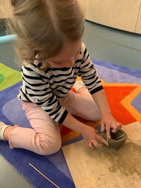 bambina che decora vasetto d'argilla