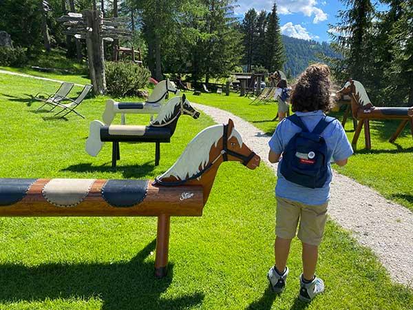 parco giochi con cavall di legno e bambin odi spalle