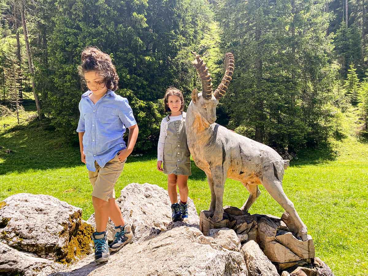 bambini con statua capriolo di legno